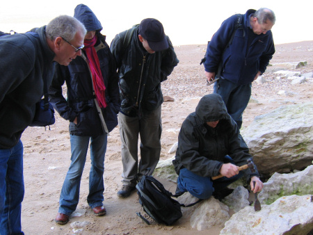 Fossil hunters extract a specimen from a boulder at Hunstanton