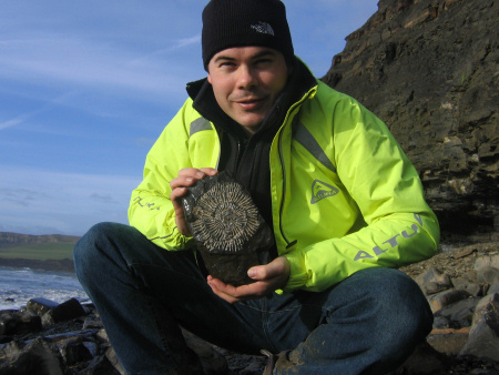 Roy Shepherd holding a fossil Subdichotomoceras websteri ammonite at Kimmeridge