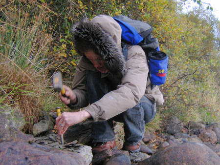 Lucinda Shepherd extracting a fossil from a rock at the River Brora